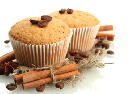 tasty muffin cakes on burlap, spices and coffee seeds, isolated on white photo