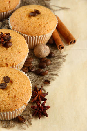tasty muffin cakes on burlap, spices and coffee seeds, on beige background photo