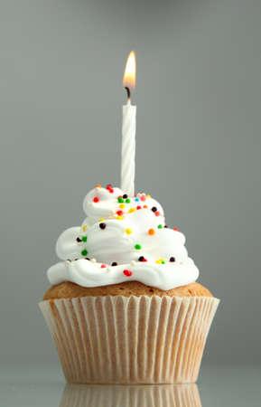 leckere birthday cupcake mit Kerze, auf grauem Hintergrund Standard-Bild