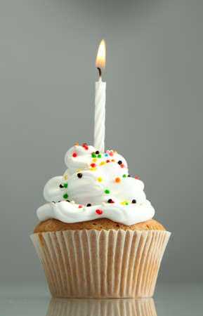 birthday cupcake: tasty birthday cupcake with candle, on grey background