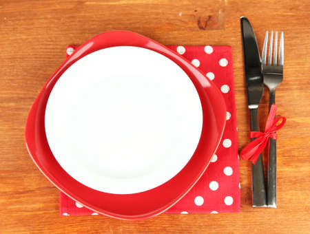 Empty red and white plates with fork and knife on wooden table, close-up photo