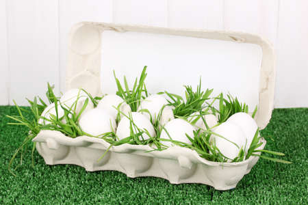 eco-friendly eggs in box on green grass on wooden background photo