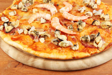 Delicious pizza with seafood on stand on wooden background photo