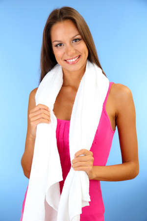 young smiling woman with towel on blue background photo