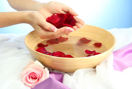 handcare: woman hands with wooden bowl of water with petals, on blue background Stock Photo