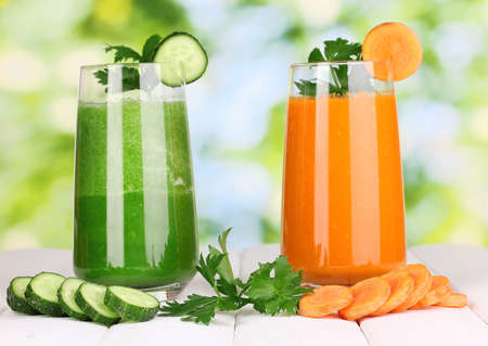 Fresh vegetable juices on wooden table, on green background photo