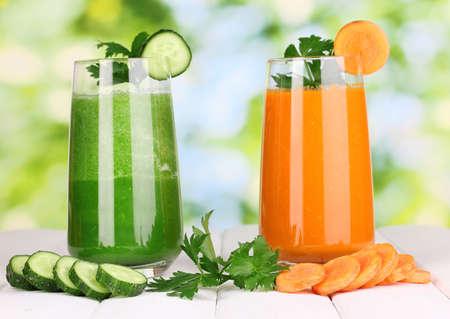 jugos: Jugo de vegetales frescos en la mesa de madera, sobre fondo verde