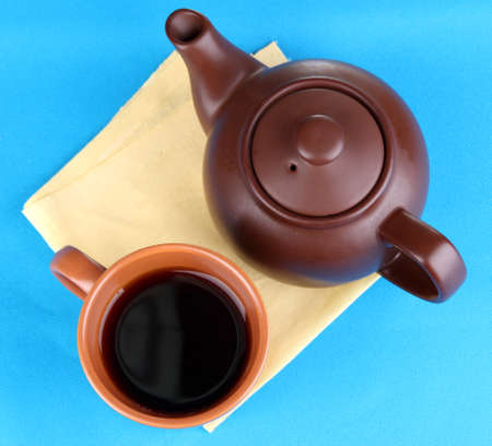 Top view of cup of tea and teapot on blue tablecloths photo