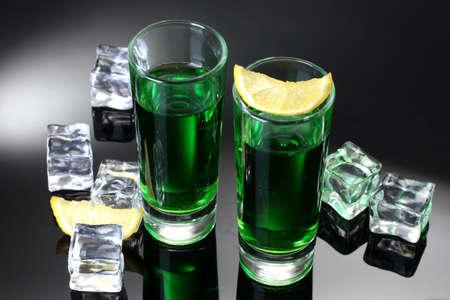 ajenjo: Dos vasos de absenta, lim�n y hielo sobre fondo gris