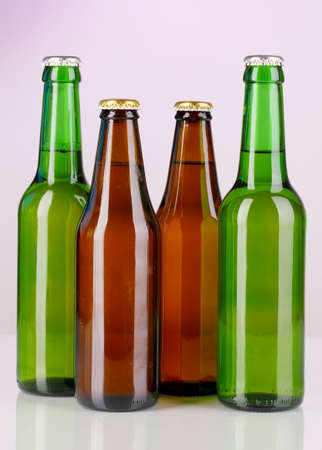 Coloured glass beer bottles on purple background Stock Photo - 16501441