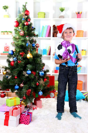 Little boy in Santa hat stands near Christmas tree with football ball Stock Photo - 16547333