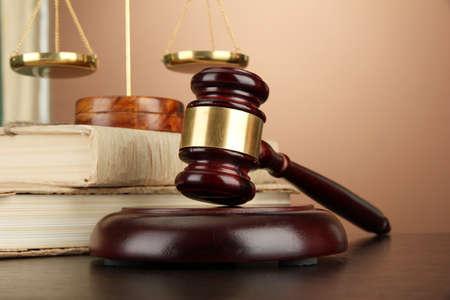 balanza de la justicia: Escamas de oro de la justicia, martillo y los libros sobre fondo marrón