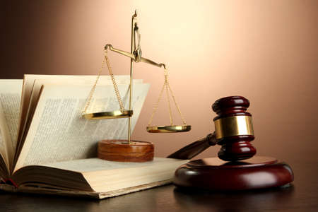 Golden scales of justice, gavel and books on brown background photo