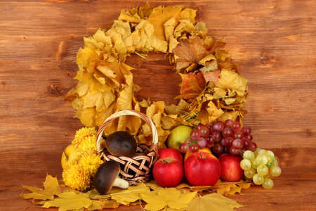 Autumnal composition with yellow leaves, apples and mushrooms on wooden background Stock Photo - 16501847