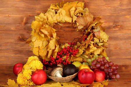 Autumnal composition with yellow leaves, apples and mushrooms on wooden background Stock Photo - 16501849