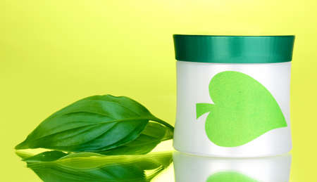 Jar of cream with green leaves on green background photo