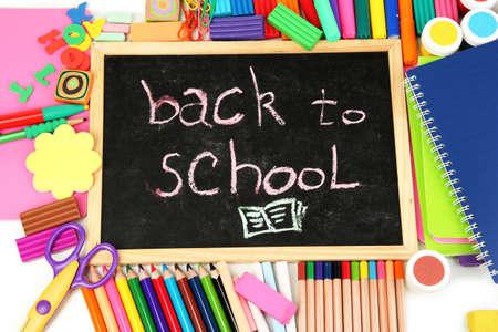 """sacapuntas: """"Volver a la escuela"""" Las palabras escritas con tiza en el escritorio de la escuela pequeña con diversas escuelas suministra primer plano"""