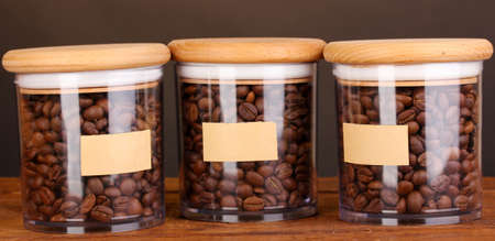 Coffee beans in jars on table on brown background photo