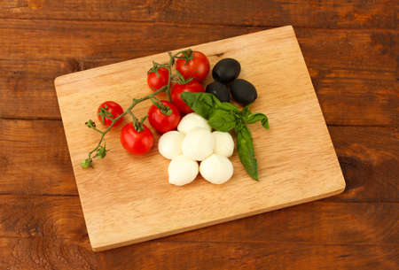cheese mozzarella with vegetables on the cutting board on wooden background photo