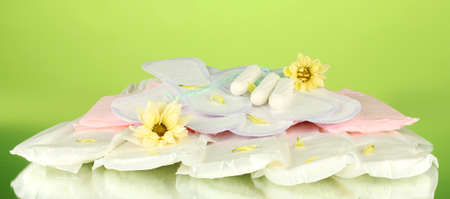 various types of sanitary pads and tampons on green background close-up Stock Photo - 16545217