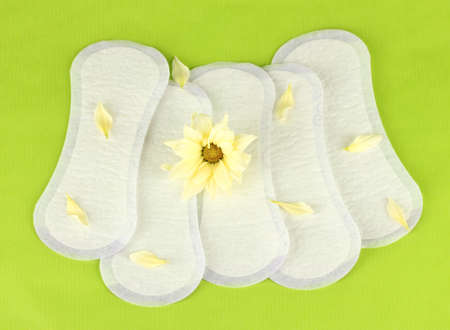 daily panty liners and yellow flower on green background close-up
