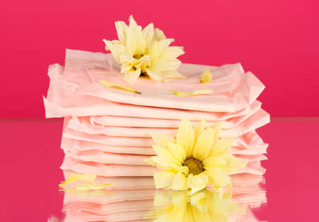 Panty liners in individual packing and yellow flower on pink background close-up Stock Photo - 16546044