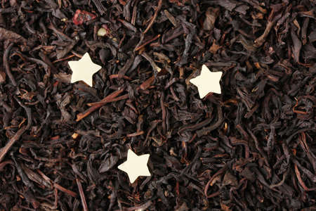 aromatic black dry tea with chocolate stars, close up photo
