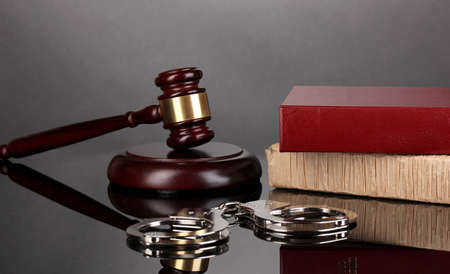 Gavel, handcuffs and books on law isolated on black photo