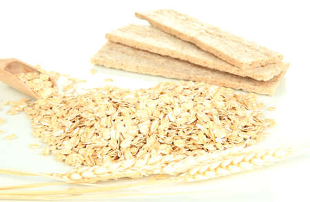 Oat flakes in wooden scoop with spikelets and oat biscuits isolated on white Stock Photo - 16546010