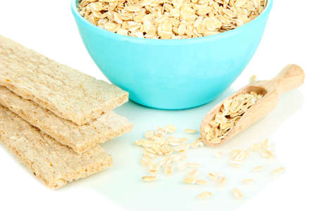 Blue bowl full of oat flakes with wooden scoop and oat biscuits isolated on white Stock Photo - 16546208