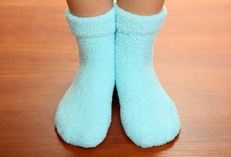 Legs female in blue socks on laminate floor photo