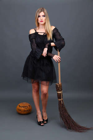 Halloween sorci�re avec un balai sur fond gris photo