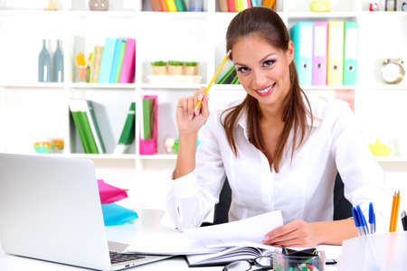 Young pretty business woman with notebook in office Stock Photo - 17051646