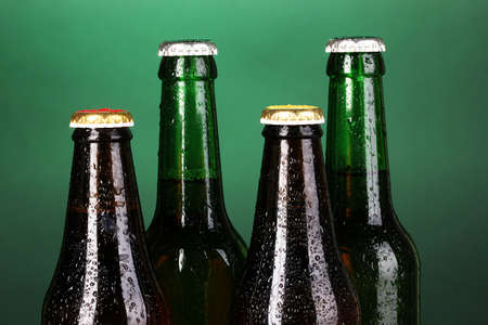 Coloured glass beer bottles on green background photo