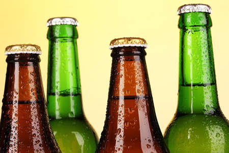 Coloured glass beer bottles on yellow background photo