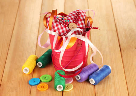 Color bucket with multicolor ribbons and thread on wooden background photo