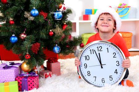 przewidywanie: Mały chłopiec z zegarem w oczekiwaniu na Nowy Rok