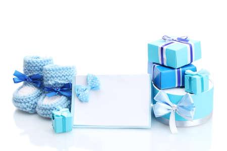 nacimiento bebe: hermosos regalos, botines del bebé y postal en blanco, aislados en blanco Foto de archivo