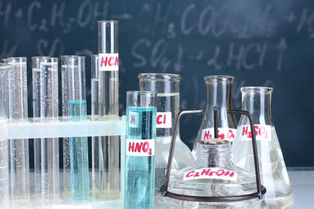 reagents: Test-tubes with various acids and other chemicals on the background of the blackboard