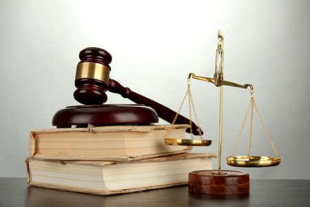 gerechtigheid: Gouden schalen van rechtvaardigheid, hamer en boeken op grijze achtergrond Stockfoto
