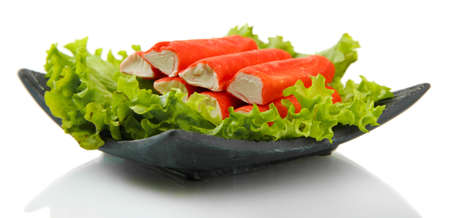Crab sticks with lettuce leaves and lemon on plate isolated on white photo