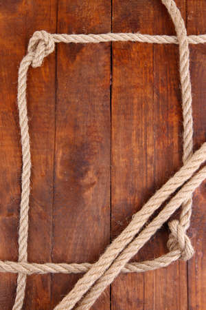 Frame composed of rope on wooden background photo