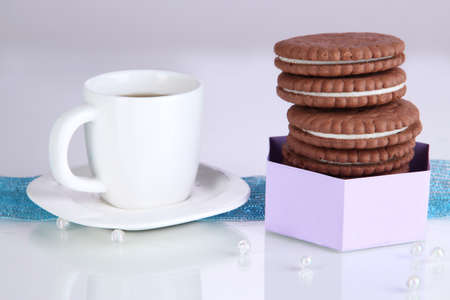 Chocolate cookies with creamy layer and cup of coffee on purple background photo