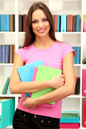 Young attractive female student holding her school books in library photo