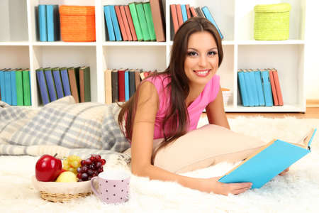 Young female relaxing on floor at home reading book Stock Photo - 17051690