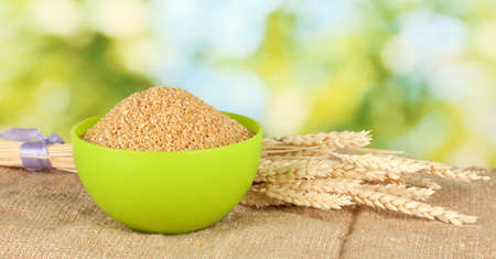 spikelets: arnautka in green bowl with spikelets on green background close-up Stock Photo