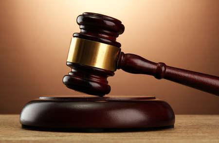 martillo juez: mazo de madera sobre tabla de madera, sobre fondo marr�n Foto de archivo