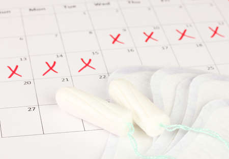 menses: menstruation calendar with sanitary pads and tampons, close-up