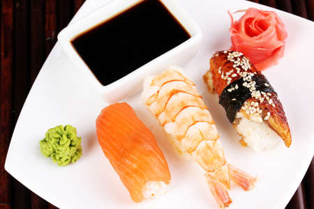 delicious sushi served on plate on bamboo mat photo