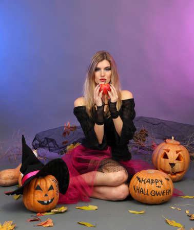 Halloween witch with red apple on color background photo
